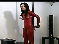 Hogtied brunette angel in red latex and high heels enjoys posing in front of the cam