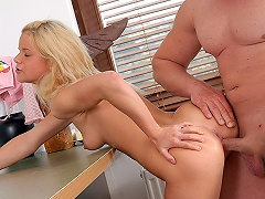 A blonde teenage girl is sitting on top of a desk. A fellow who is next...