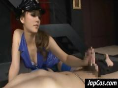 Fleshly Asian officer, in purple latex, gives her prisoner a handjob
